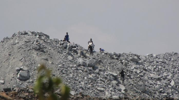 Young men searching for gold, waste dump at North Mara mine